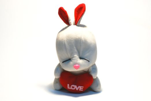 Rabbit sits and holds in paws red heart, a symbol of love