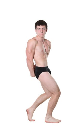 The young athlete the man poses on a white background