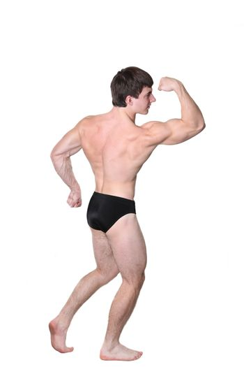 The young body builder poses with greater muscles on a white background