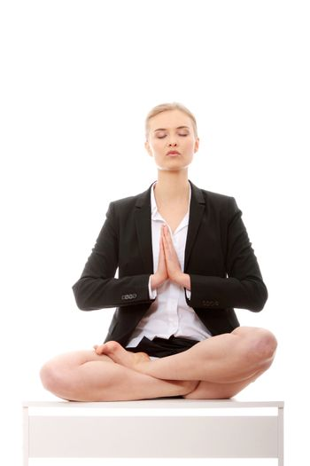 Beautiful blond businesswoman sitting on white desk in lotus flower position of yoga. Isolated on white