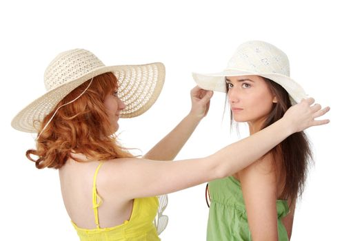 Two girlfriends in summer dress and hat over white background