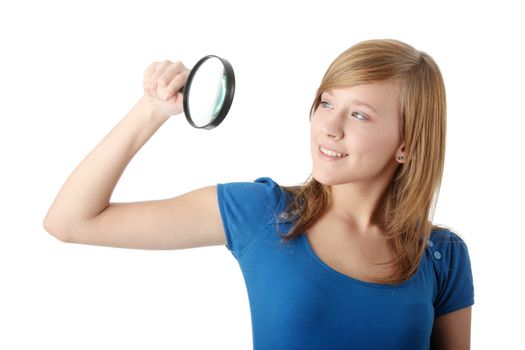 Young attractive smiling teen woman looking into a magnifying glass, isolated