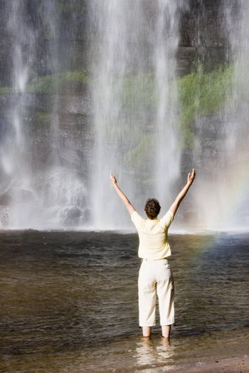 Woman standing in front of a tropical waterfall