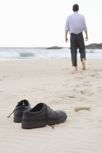Businessman walking barefoot on a beach. Focus on his shoes in the foreground.