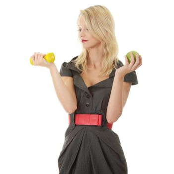 Young blond woman with green apple and yellow dumbbell - healthy living concept