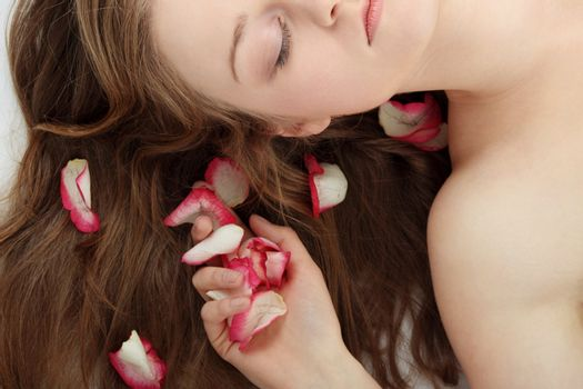 Close-up of beautiful young woman face with long blond hair and rose-petal