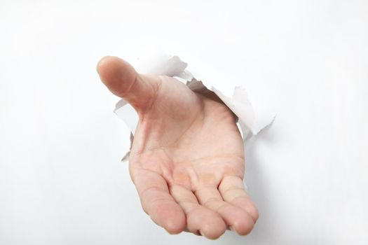 Hand punching through white  paper and try to shake or take some one
