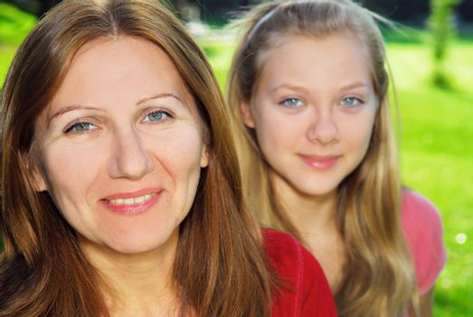 Portrait of smiling family of mother and her teenage daughter
