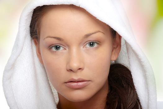 Beautiful young caucasian woman in bathrobe after bath calm portrait.