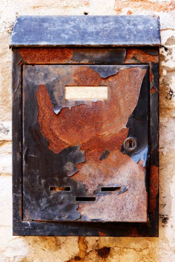 Old rusty mailbox on the shabby gate in Italy