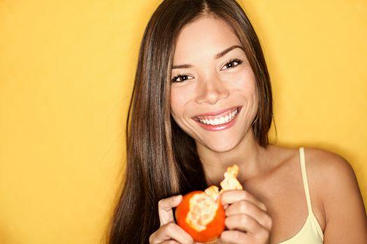 Woman eating orange