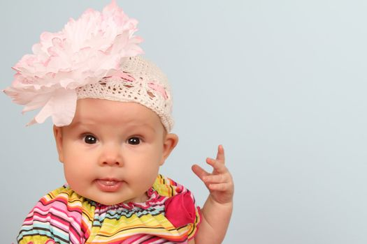 Cute baby girl wearing a beanie with large flower