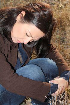 Beautiful brunette female sitting alone in a field