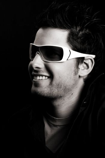 Attractive male wearing sunglasses against black background