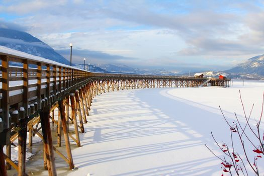 Wooden pier with snow at frozen lake in Salmon Arm