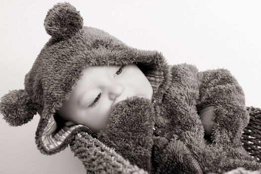 Four month old baby boy wearing a fully bear suit