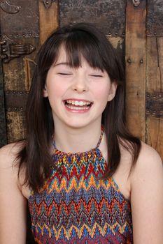 Beautiful brunette teen against a wooden background