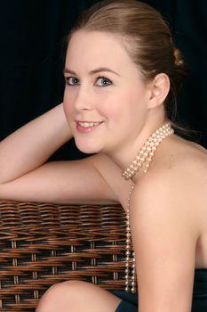 Beautiful blond female wearing pearls against a dark background