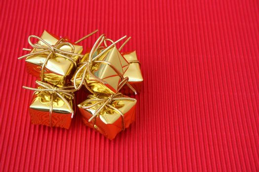 Small golden christmas gifts on a red background