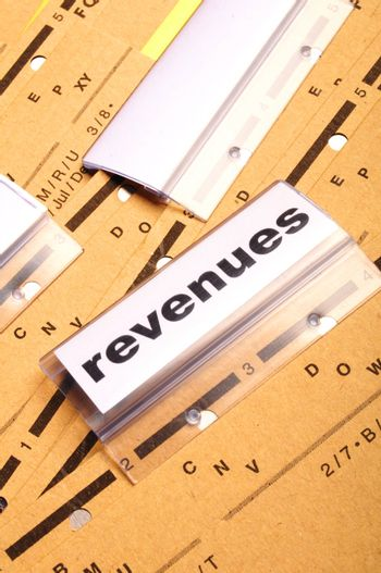 revenue or revenues word on business office folder showing financial success