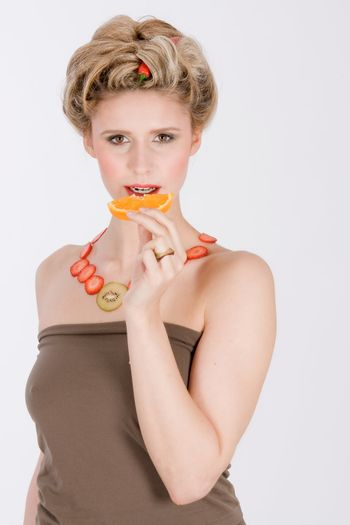 Young woman with a necklace made of strawberries and kiwi eats an orange