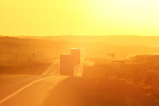 Semi trucks and sun glare along Trans Canada Highway