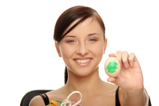 Young caucasian woman making easter decorations, over white background