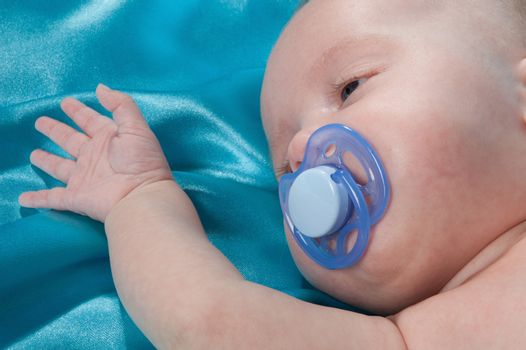 a sweet baby sleeping on a blue satin sheet