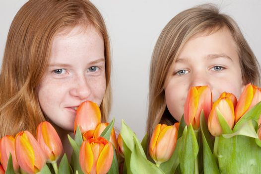 two young girls are holding pink orange tulips
