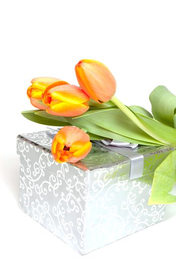 yellow orange tulips laying on a silver present
