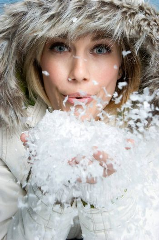 Pretty winter woman blowing snow