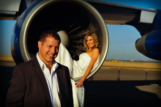 sexy young adult wedding couple laying inside the engine intake of Boeing passenger aircraft with groom in front