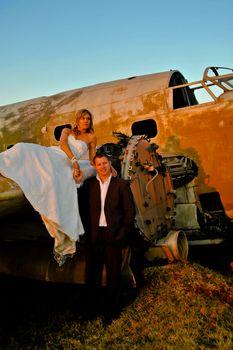 sexy young adult wedding couple standing at crashed DC3 Dakota war plane