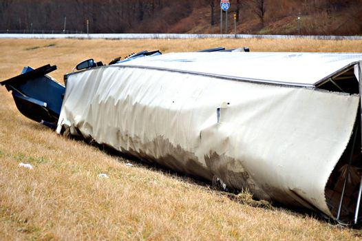 A tractor trailer on its side in the median after a roll over accident.