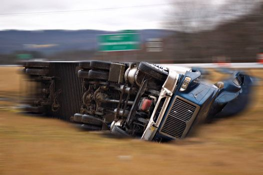 A tractor trailer on its side in the median after a roll over accident. Blur effect added to simulate motion.