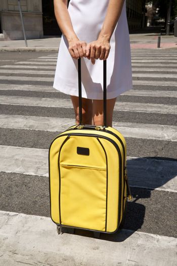 woman with yellow suitcase on crosswalk