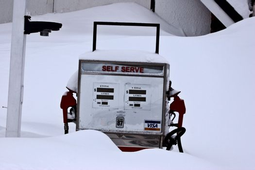 Old gasoline pump covered by snow