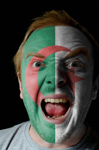 Low key portrait of an angry man whose face is painted in colors of algerian flag