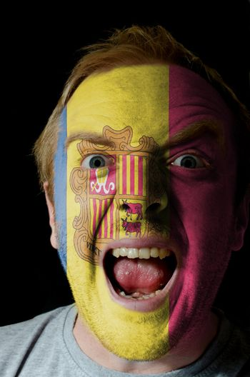 Low key portrait of an angry man whose face is painted in colors of andoran flag