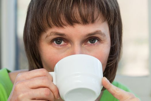 Closeup portrait of woman drinking coffee from a white cup