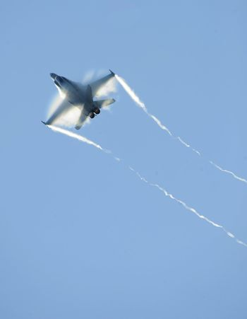 An airforce jet fighter streaks through the sky.