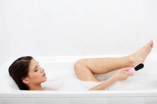Woman in bath rubbing heel of foot