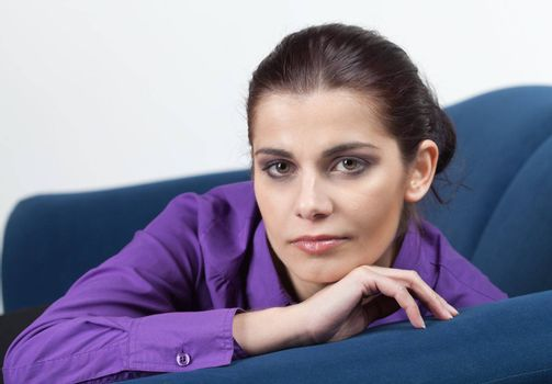 Pretty young brunette woman resting on blue couch