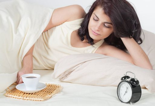 Young woman in bed holding a cup of coffee after she waken up