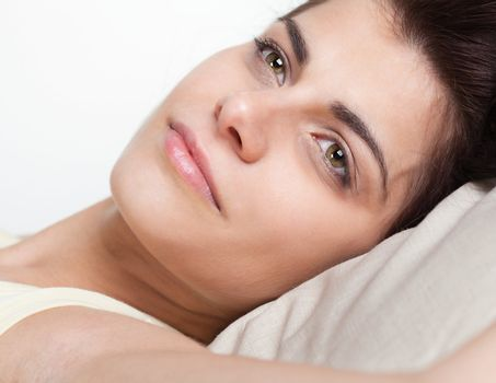 Closeup portrait of pretty young woman in bed