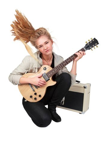 Blond rock teenage girl playing an electric guitar on her knees. Studio shot, isolated on white background.