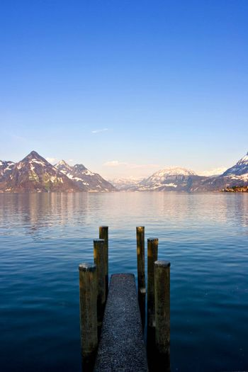 Empty dock in calm lake with mountains in the horizon. Buochs, Switzerland.