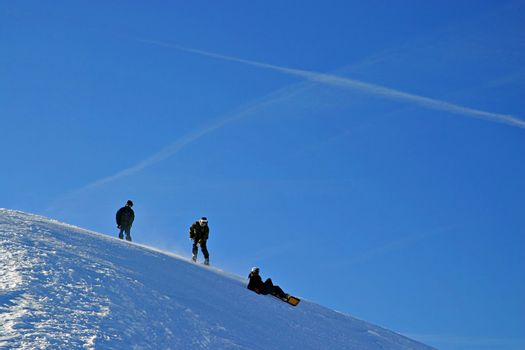 Snowboarders on slope, with blue sky.