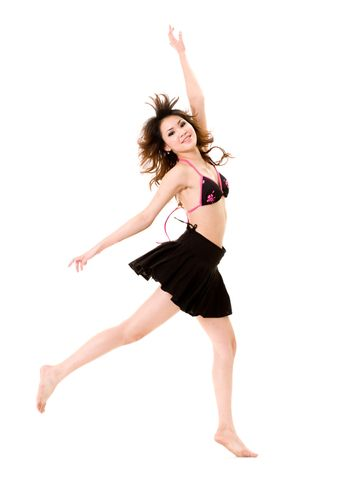young woman in bkini top & skirt jumping freely and happily