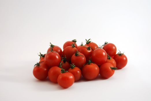 Fresh cherry tomatoes loose on white background.